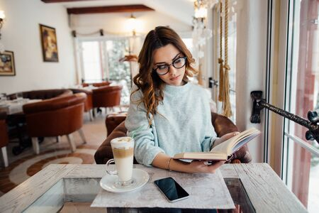 Woman in glasses reading book in cafe while drinking coffee