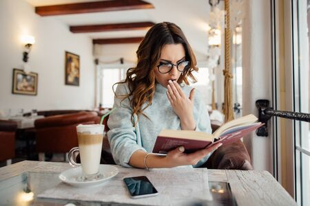 Emotional girl in glasses reading book in cafe while drinking coffee