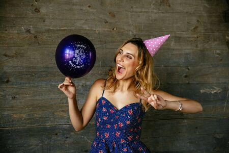 Cheerful attractive girl having fun while celebrating birthday, showing peace gesture, looking at balloon. Wearing dress, festive hat, curly hair. Holiday concept.