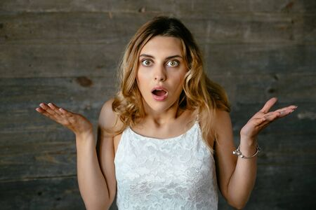 Young pretty woman shocked about something, misunderstanding, spreads out her hands. Dressed in white singlet. Stock Photo