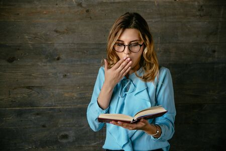 Young pretty woman in eyeglasses looks shocked, cover her open mouth with hand while reading a book. Dressed in elegant blouse.