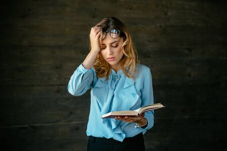 Exhausted woman looks tired, holds a book, keeps her head with hand, eyeglasses on forehead, overworked. Dressed in blouse. Archivio Fotografico
