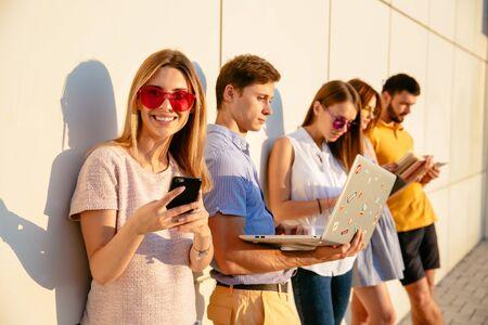 Hermosa mujer con gafas de sol rosas sonriendo a la cámara y usando teléfono móvil. Grupo de personas que utilizan tecnología de comunicación sobre fondo de pared al atardecer