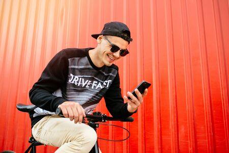 Hombre joven de moda con gorra y gafas de sol mirando la pantalla del teléfono inteligente, viendo una película divertida, mientras descansa en bicicleta, cerca de la muralla urbana. Foto de archivo