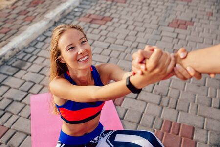 Male helps a lovely fitness woman to get up after doing a sport exercise on carpet. Healthy Lifestyle.
