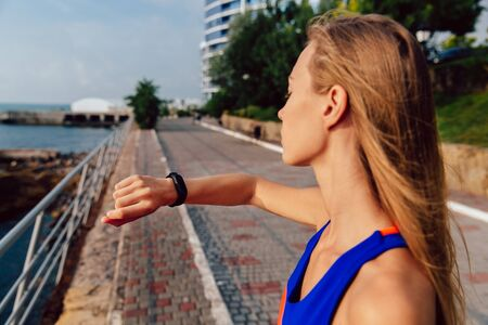 Side view of attractive blonde sportswoman checking a cardio and time after workout on the quay, near the ocean.