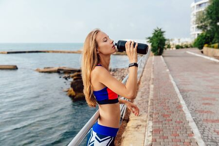 Side view of lovely sportive girl with long blonde hair drinking a water from bottle after jogging during workout outside, near the sea. Stock Photo