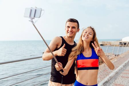 Happy attractive couple in sportswear showing a thumb up and peace sign while taking a selfie on mobile phone, after workout outdoors, near the sea.