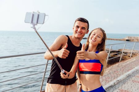 Funny happy couple in sportswear showing a thumb up while taking a selfie on smartphone, after workout outdoors, near the sea.