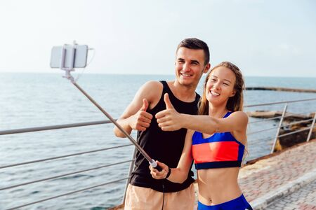 Joyful sportswoman and sportsman in sportswear showing a thumb up while taking a selfie on smartphone, after workout outdoors, near the sea.