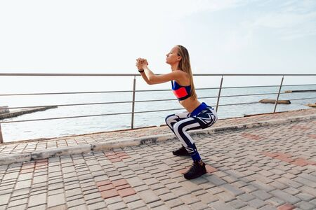 Side view of blonde beautiful girl doing squats during workout on the quay, near the sea, wearing sport tank top and leggings. Full length.