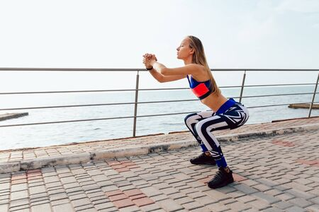 Side view of pretty sportswoman doing squats, sports exercises for body during training on the quay, near the sea.