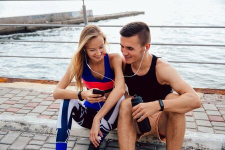 Front view of lovely sportswoman and attractive sportsman watching a funny video on mobile phone, while sitting on the ground and resting after workout, near the sea