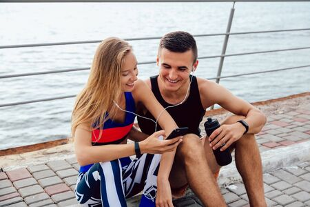 Happy sportswoman and smiling sportsman looking at smartphone screen and watching a funny video in headphones, while sitting on the ground and resting after workout. On the quay, near the ocean.