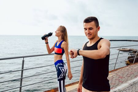 Happy muscular guy checking a cardio and time after running, while a fitness girl drinking a water after running a distace. Outdoors, near the ocean. Stok Fotoğraf