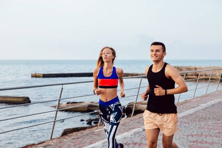Sportive young man and woman in sportswear jogging together on the quay near the ocean. Workout on quay. Stock Photo