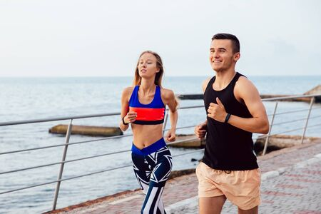 Attractive man and woman in sportswear running together on the quay near the sea. Workout on quay. Sport concept.