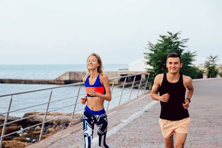 Joyful attractive guy and beautiful girl working out outdoors, running together on quay, near the sea. Healthy lifestyle. Stock Photo