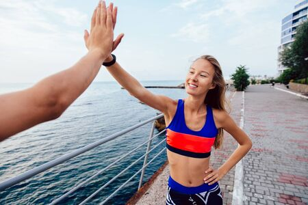 Lovely young fitness girl giving her friend a high five after running a marathon, standing on quay near the sea. Sport concept.