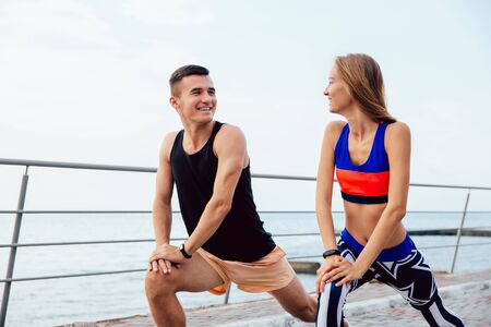 Smiling sportive couple doing sports exercises, looking at each other, while stretching a body, during workout on the quay.