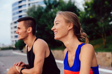 Young beautiful couple practicing sport outdoors, stretching, doing exercises, enjoying healthy lifestyle. Outside.