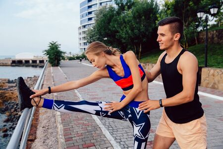 Athlete guy helps his girlfriend stretching legs, during workout on the quay, near the sea. Sport concept.