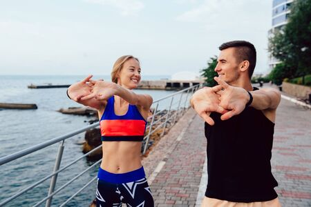 Cheerful beautiful girl and handsome sportive man looking at each other while working out on the quay, near the ocean. Healthy lifestyle.