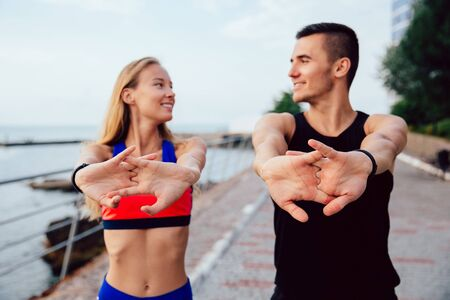 Happy man and smiling woman doing stretching exercises for arms during workout on the quay. Dressed in sportswear.