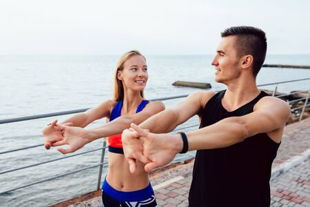 Lovely girl and handsome man looking at each other while doing stretching exercises for body during workout on the quay. Sport lifestyle