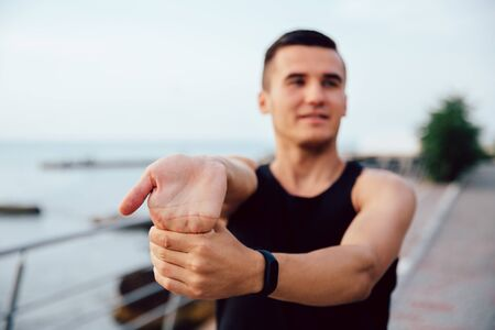 Handsome sportive man doing exercise for arms, working out on the quay, near the sea. Sport concept.