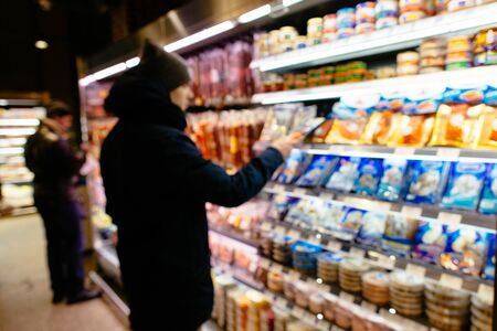 Shopping in supermarket. Man chooses product on shelve in supermarket. Blurred photo