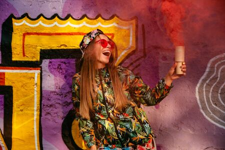 Stylish pretty girl in red eyeglasses wagging red smoke bomb, smiling cheerfully, standing near the wall with graffiti. Dressed in colorful jacket and cap.