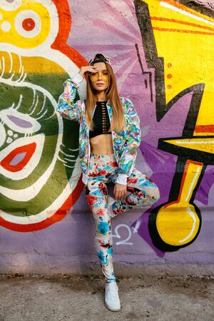 Beautiful stylish model in sunglasses standing on background of wall with colorful graffiti. Dressed in fashionable suit, tank top and cap. Outdoors. Stock Photo