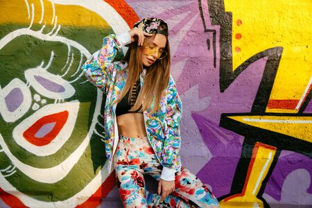 Young stylish woman, dressed in bright suit, cap, in sunglasses, standing on a graffiti wall background. Outdoors.