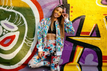 Lovely funny girl in eyeglasses, standing on background of wall with graffiti. Dressed in bright suit, black tank top and cap. Outdoors.