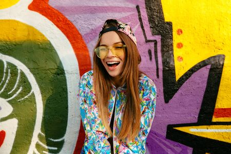 Smiling beautiful girl in sunglasses, winking, looking at camera. Dressed in stylish jacket and cap, standing on the wall background with a graffiti. Street fashion.