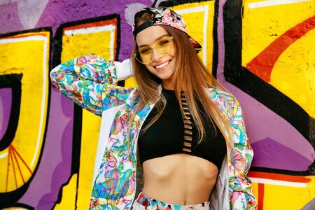 Bright model, smiling cheerfully, standing against the wall with graffiti. Dressed in singlet, colorful jacket and cap, in sunglasses. On the street.
