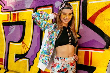 Trendy girl, smiling cheerfully, standing against the wall with graffiti. Dressed in singlet, colorful jacket and cap, in eyeglasses. Outdoors.