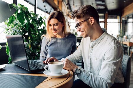 A couple sitting at cafe smiling cheerfully, using a laptop, spending time with pleasure, drinking coffee. Dressed in casual clothes.