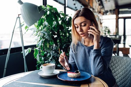 Beautiful young woman talking on smartphone, while eating a dessert with cup of coffee, sitting at cafe.