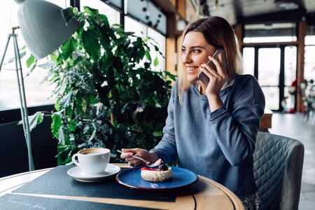 Smiling amazing girl eating cheesecake while talking on smartphone, enjoying resting time at cafe. Dressed up in sweater.