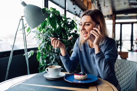 Cheerful pretty girl eating dessert while talking on smartphone, enjoying resting time at cafe with cup of coffee. Modern interior.