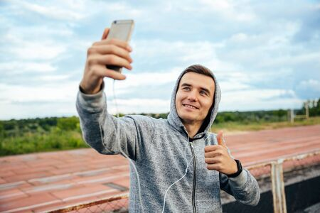 Close-up portrait of young smiling man taking selfie with smartphone, showing a thumb, wearing sweatshirt with hood, outdoors