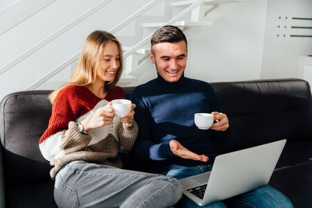 Beautiful happy young couple discussing a movie while watching it on laptop, smiling, sitting on couch and drinking tea at home.
