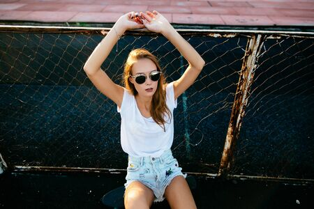 A beautiful girl sitiing near the fence  with her hands up on the sunset.