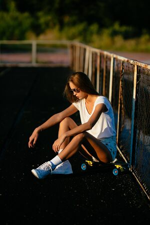 A beautiful woman looks downstairs while sitting on her skateboard.