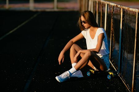 A sexy woman looks downstairs while sitting on her skateboard.