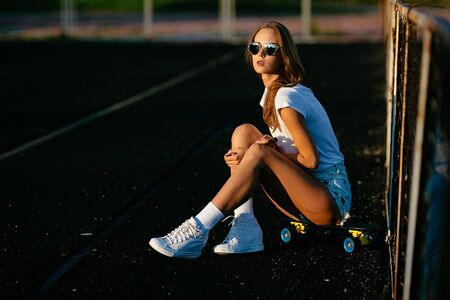 A good looking teen sitting after skating with her sunglasses on.