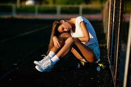 Tired beautiful young girl after skating.