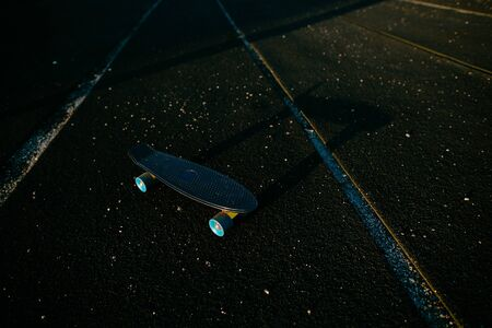 Black penny skateboard on the black sport field.